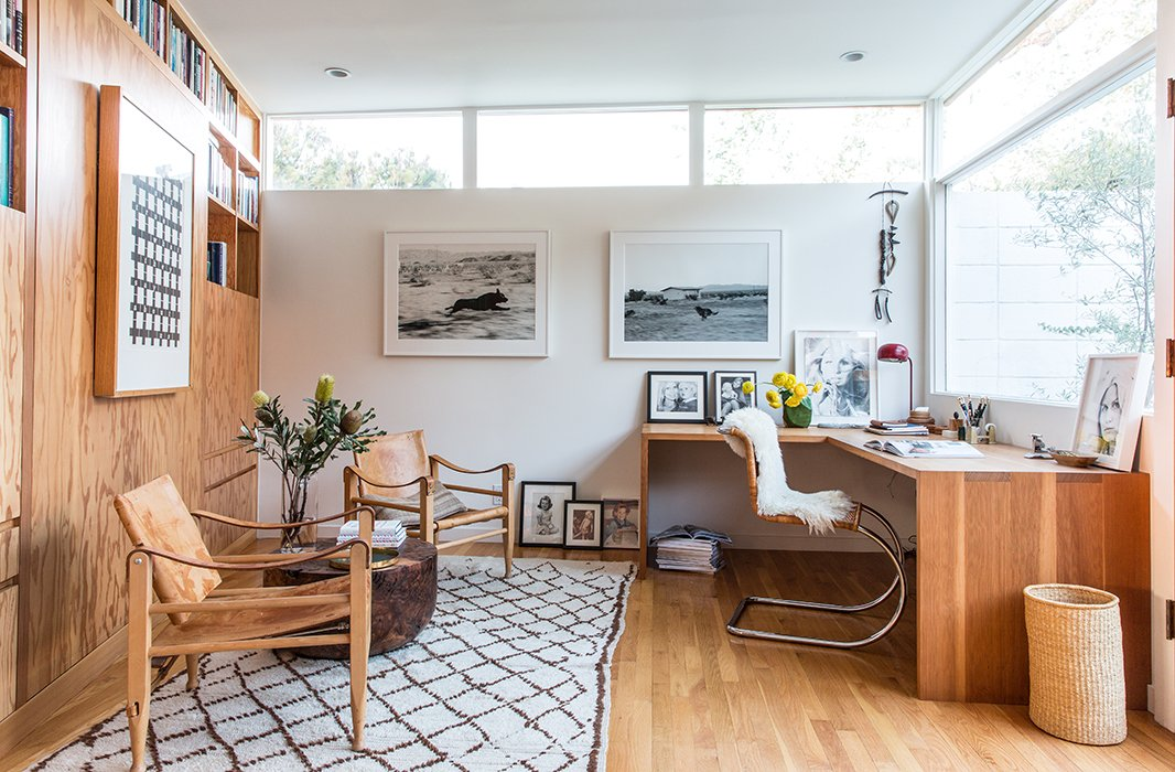 The office doubles as a guest room courtesy of a Murphy bed and side tables hidden in the built-in bookshelves. Jed crafted the L-shape Douglas fir desk. Two Kaare Klint Danish safari chairs flank an Alma Allen table. The photographs are by John Divola.