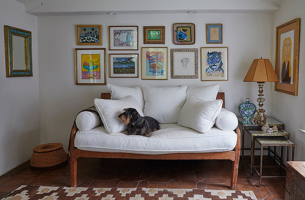 "In the office, a wall of personal artwork surrounds an Indian sofa. ""There's a portrait of my grandmother, a colorful monkey my friend painted,, and I did the blue tiger when I was 12,"" Kendall says. The Moroccan rug is from a favorite local shop, Upstairs at Pierre Lafond."