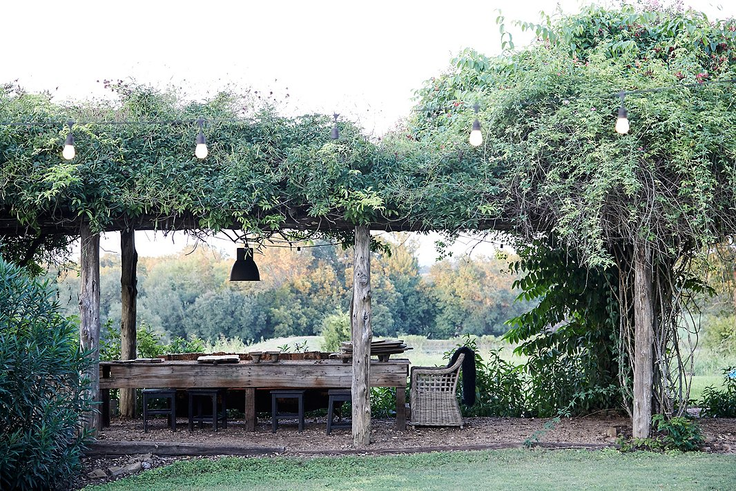 A rustic pergola covered in overgrown vines is one of the property's many outdoor dining and lounge areas.