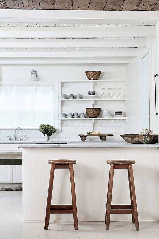 Sleek ceramics, weathered woods, and woven textures give Holly House's open kitchen a laid-back look.