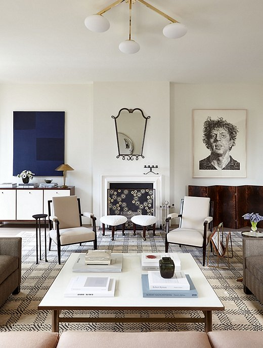 In this Manhattan apartment designed by Alyssa, the abstract painting on one side of the fireplace adds the perfect dash of color, just as the metallic glints of the ceiling light and the lamp atop the credenza contribute an ideal touch of glimmer.