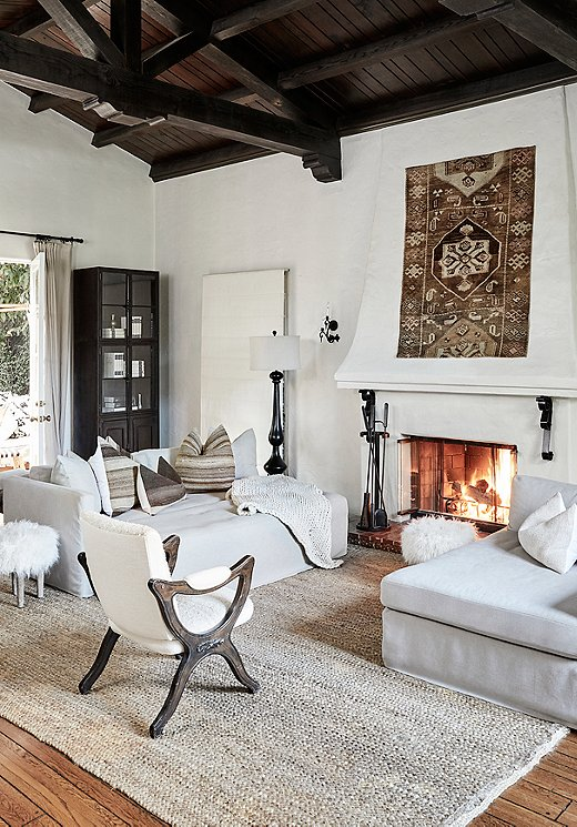 """Tammy's signature pillowsbring texture to the living room, while sheepskin elements add warmth. Kilim touches, like the highback vintage chair upholstered in a Berber kilim piece, add another layer of sophistication. She also opted to display one rugas art, placing it center stageover the fireplace. """"That particular piece pulled the whole room together,"""" Tammy says."""