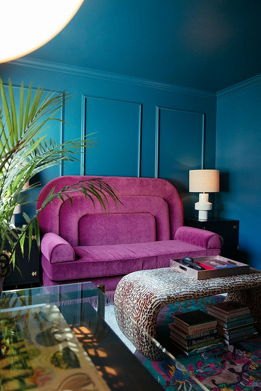 The purple sofa is Jessie's custom design. Dubbed the ShaSha,it sits in Jessie's office andtransforms into a pull-out bed when guests stay over. Exaggerated arches and a grand silhouette play on the Regency style Jessie incorporated in her design.
