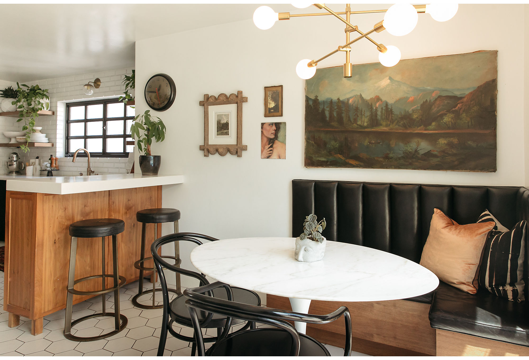"""Jessie purchased the landscape art in her breakfast nook from a vintage dealer turned friend. """"I talked him into selling it to me. It was one of his favorites and he didn't want to let it go,"""" she says. She paired it with a leather channel-back booth and a Sputnik-style light to give it a mod vibe. Velvet pillows add an extra layer of glam."""