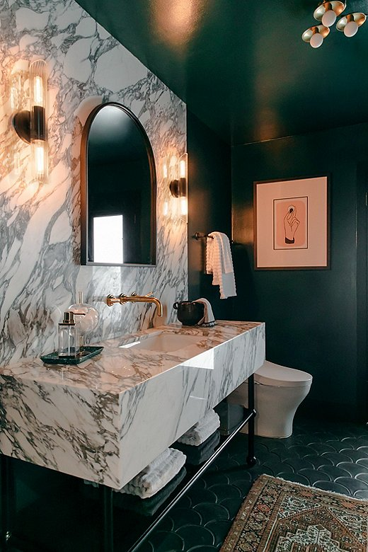 Jessie went moody in the main bathroom, painting the space Night Watch by Benjamin Moore. Black-and-white marble steals the show, while the sconces and the arched mirror add a touch of Deco glam.