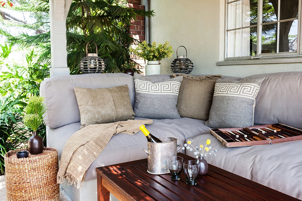 "For a versatile look, choose neutral pieces like this gray couch. ""I can change the vibe by swapping in sheepskins and funky pillows,"" says Stansfield. ""If I'm having a Fourth of July party, I can put vintage American flag pillows out and bunting for a completely different look."""