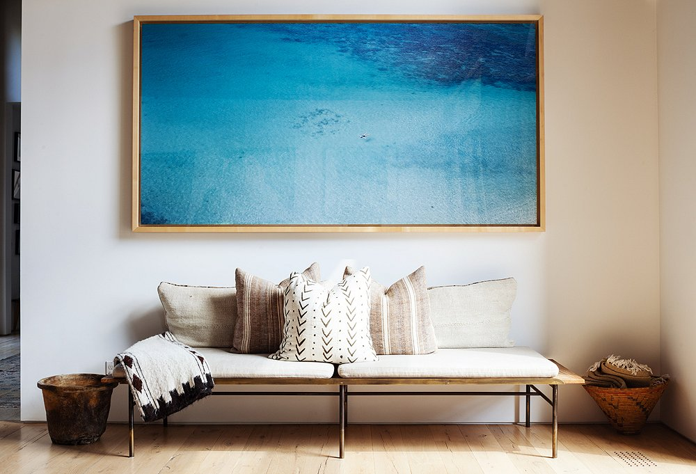 A Richard Misrach photograph was the perfect solution for a blank living room wall. The welcome burst of color fits in thanks to the neutral vintage textiles below—some are rugs turned into pillows.