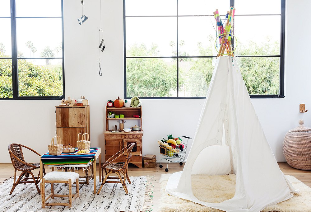 """I love a tepee,"" Kayne says. ""It's so fun."" A sheepskin rug adds a cozy layer in a room where everything is kid height and floor play is a regular activity."