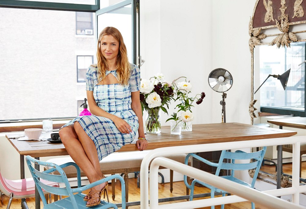 Ronson atop her dining table, wearing a dress of her own design and Tabitha Simmons shoes.