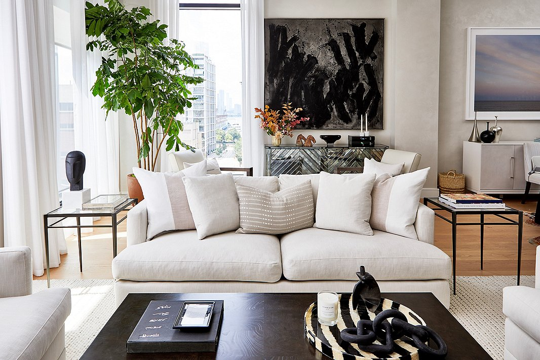 """""""I always wanted a neutral and pale living space but shied away from it in our last apartment because of our kids,"""" Ashley says. """"I was nervous to ask Jess to go with this look, but rather than discouraging me, she took the challenge and we made it work!"""" It helps that the Hudson Sofa is upholstered in eco-friendly Crypton fabric, which repels spills and stains. Find the tray on the coffee table here; find the sculpture on the side table here."""