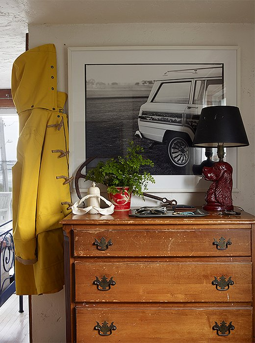 In the bedroom, a lamp made from a ceramic bust of a spaniel sits atop a Federal-style dresser in front of one of Matt's photographs. The classic yellow raincoat is also his.