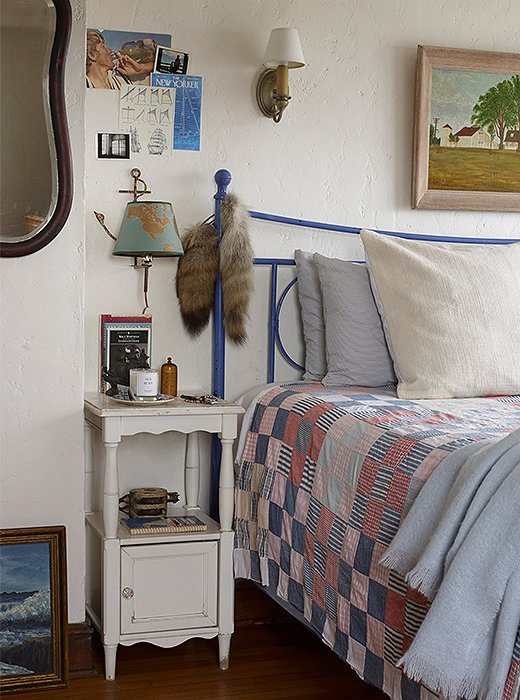 Beside a bed frame sits a nightstand unencumbered by a table lamp. Instead, a brass sconce shaped like a fishing lure was hung, making the most of a spare space on the white plaster wall.