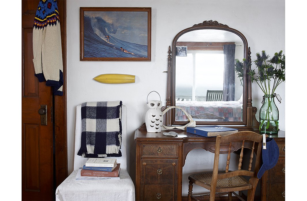 A Queene Anne dressing table is paired with a spindle-back chair and a ceramic owl. A print from yesteryear depicting two surfers hangs next to the closet door draped in Fair Isle.