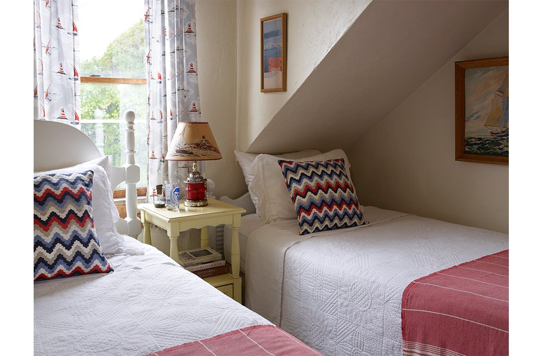 The cheery guest room features twin beds and a ship light-turned-lamp shaded by a coastal scene. Quilts, in lieu of duvets, are in line with Matt's affinity for handcrafted things.