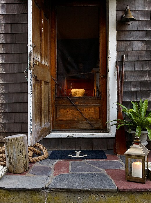 Outside, a gravel path leads to a slate porch. Styled with an old tree stump, an anchor mat, and a brass lantern, it hints at the nautical charm found within.