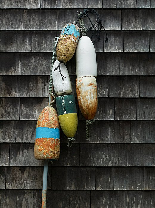 A string of old buoys provides a pop of color against the exterior's weathered shingles.