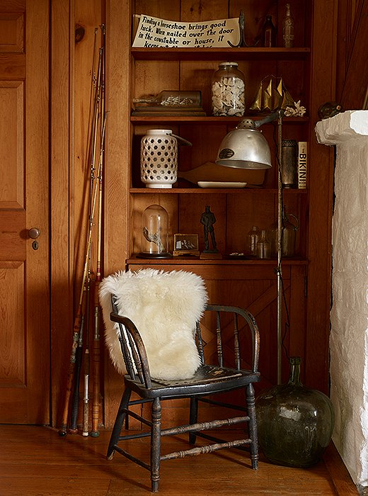 A captain's chair draped with a sheepskin creates a cozy corner next to the living room's fireplace. Behind, a built-in bookshelf lined with thrifted treasures reads as an open-air cabinet of curiosities.