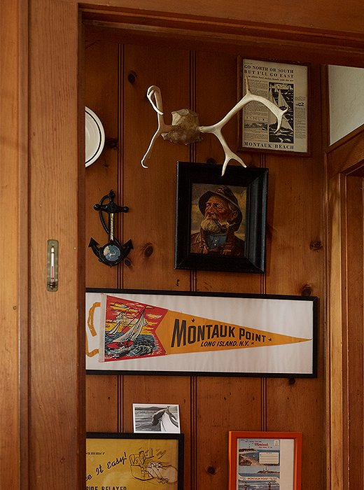 At the bottom of a staircase hangs a captain's portrait, a pair of antlers, and a framed Montauk flag.
