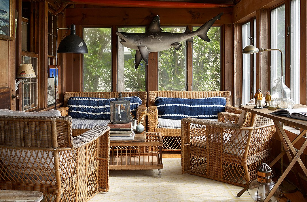 In the sunroom, a wicker sofa and chairs are lined with shibori cushions. The shark is a nod to one of Matt's favorite films, while the industrial floor lamp adds heft, height, and a sense of scale.