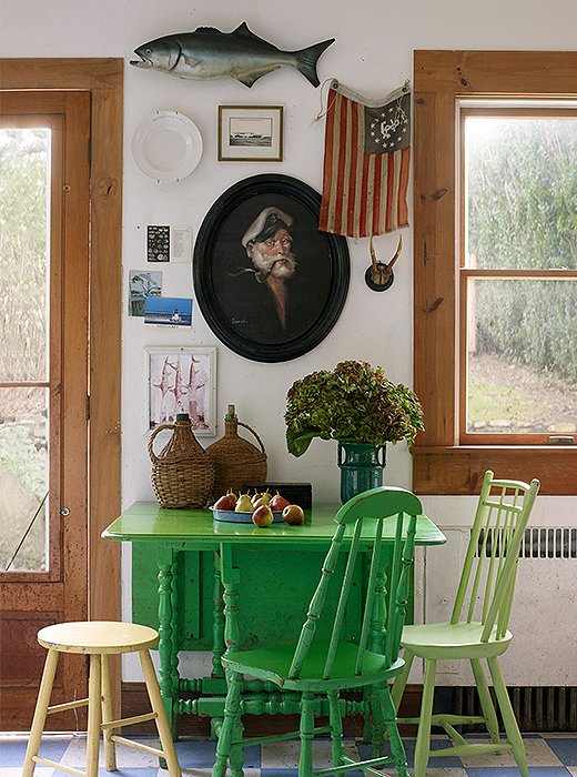 Surrounded by mismatched chairs, the well-used table in Williamsburg green is the kitchen's colorful focal point. Behind, an Americana-inspired gallery wall features yet another captain, an odd plate, and a Revolutionary flag. On the floor, blue-and-white linoleum offers (an original) retro touch.