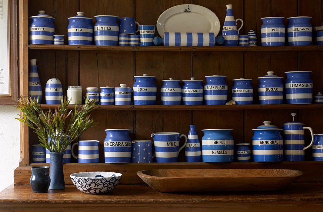 "Rows of striped jars hold dry goods on a freestanding pantry made of pine. Simple, functional, and visually appealing, it's a vignette that proves Lisa Birnbach's point about a ""successful marriage of utility and excellence."""
