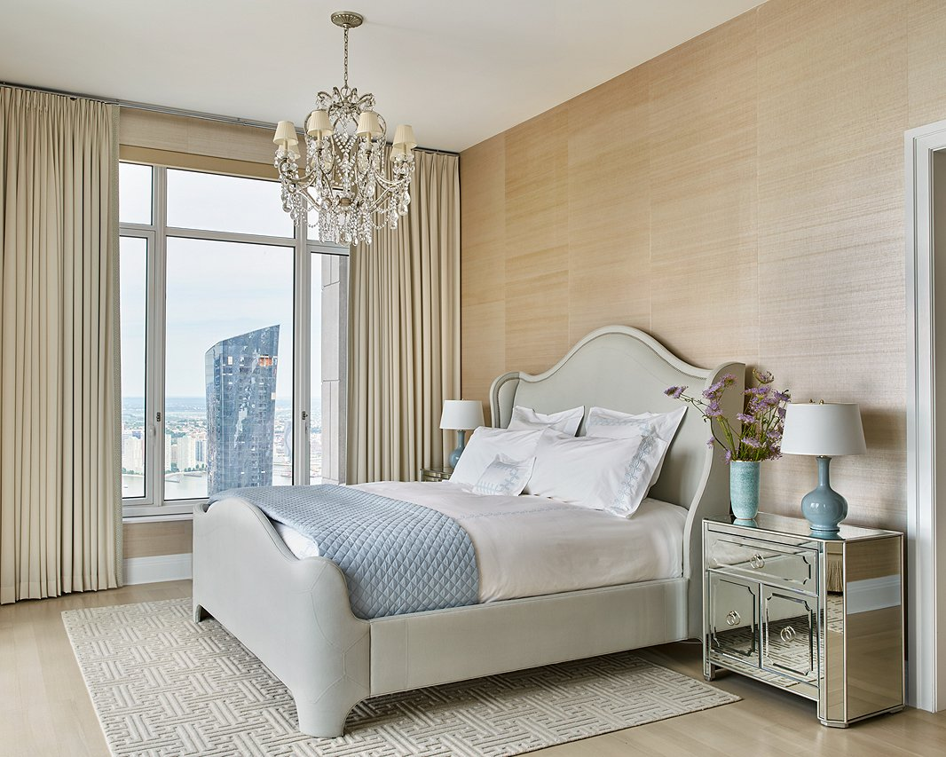Serene shouldn't mean boring. Here icy blue accents, mirrored nightstands, and a sparkling chandelier, along with the tonal patterns of the rug, wallpaper, and quilt, add just enough intrigue. Room by Ariel Okin; photo by Seth Caplan.