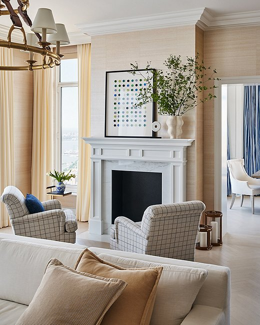 "A traditional aesthetic isn't as constricting as you might think. Ariel opted for this pop of modern art by Dawn Wolfe, a favorite artist of hers, to shake up the feel of the room. ""Something super poppy and graphic above the mantel works well because it feels unexpected paired with the men's suiting fabric on the more traditional club chairs,"" Ariel says."