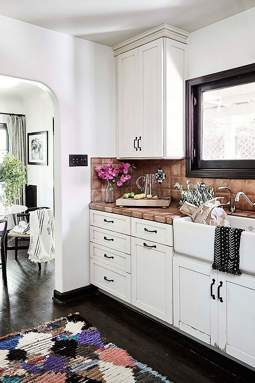 Galley kitchens are standard fare in 1920s Spanish Colonial homes. Abigail loves to entertain, with the outdoor space serving as the major hot spot in her home. The colorful rug, an unexpected choice for a lover of white, works well with the terracotta tiles.