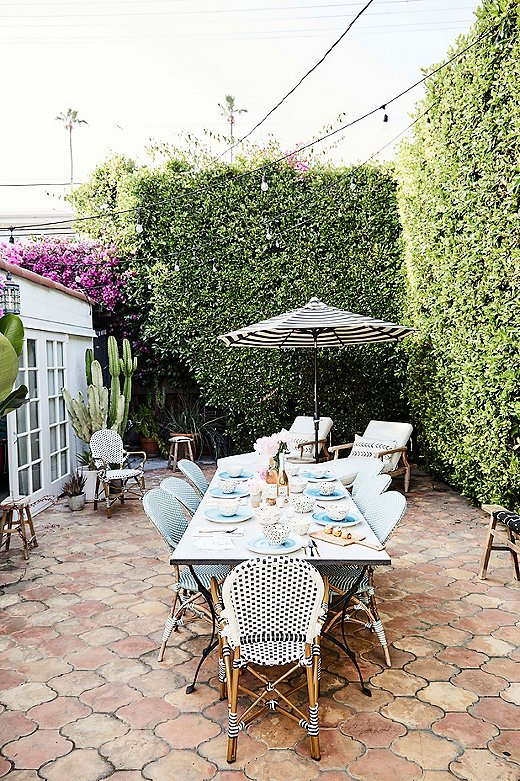 """It's a pretty amazing space for entertaining,"" says Tammy of Abigail's backyard. She already had the blue and black bistro chairs, so Tammy added benches from Fragments Identity for extra seating."