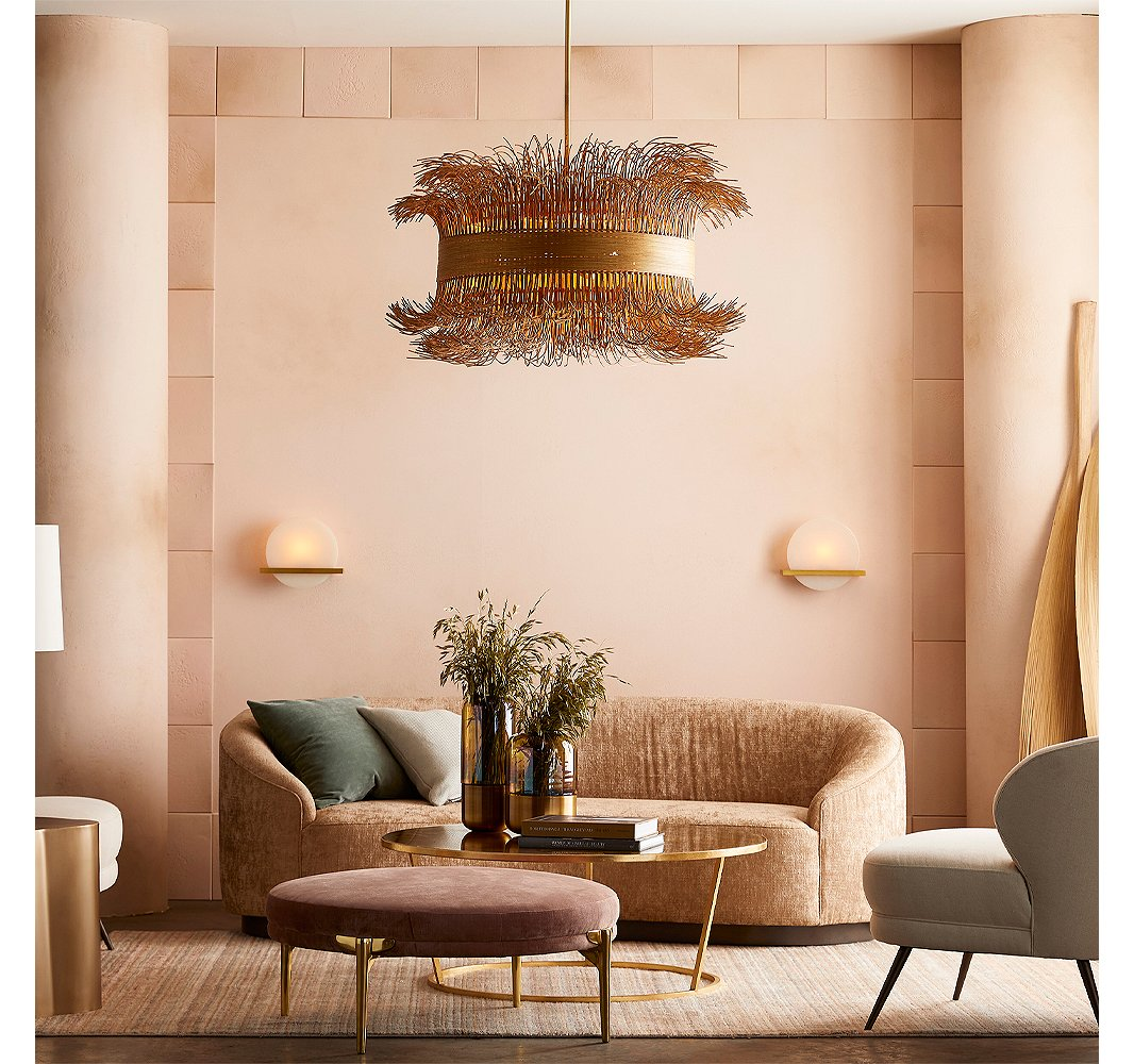 With its barely tamed rattan fringe (cinched with steel in a gold finish), the Filamento chandelier by Laura Kirar provides an organic counterpoint to the sleek and sophisticated Savion sconces made of onyx and steel. Likewise, the slender straight and splayed legs of the ottoman and the chair contrast with the curves dominating the room.