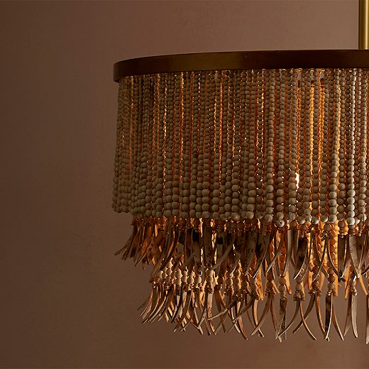 The Baja chandelier pairs organic ease (wood beads, coconut-shell fringe) with metallic sophistication (the brass-finish iron frame).