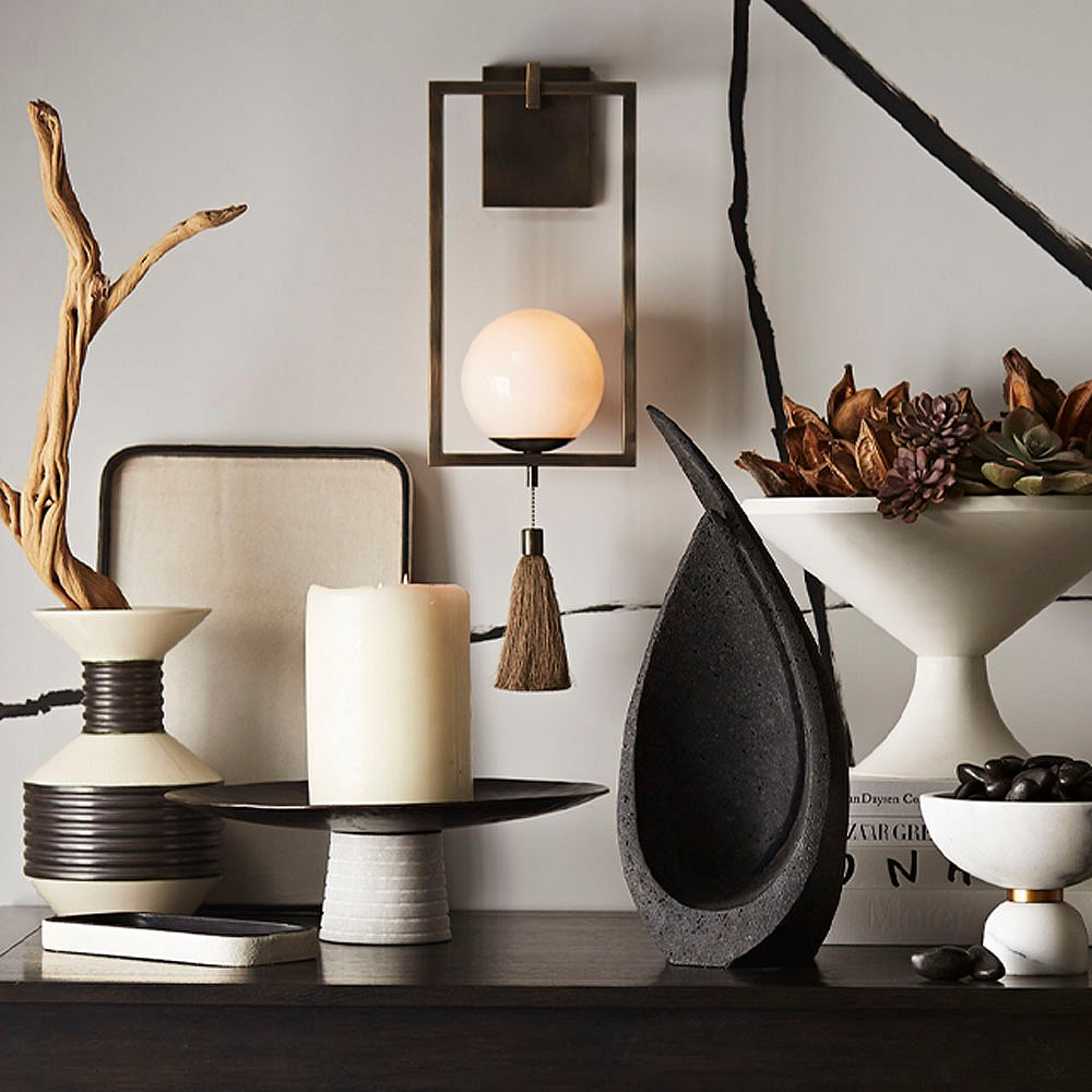 In the center of the above tableau is the Trapeze sconce by Ray Booth in an antique-brass finish. Other pieces include the charcoal Celine sculpture and the concrete Cayden centerpiece (which can also be used as an outdoor planter), and the white marble Tate container.