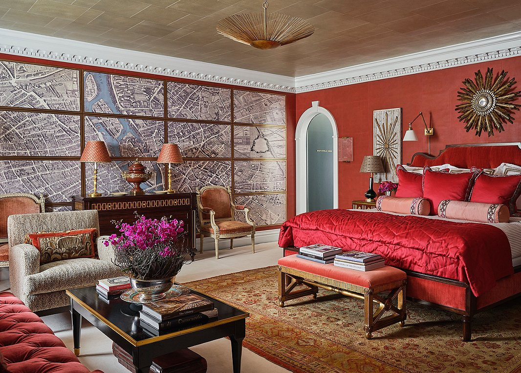 """""""Everyone says you can't do a red bedroom, and the contrarian that I am wanted to do it,"""" laughs Alexa Hampton. The seemingly multipart wall map of Paris is actually a trompe l'oeil work from a new collaboration between Alexa Hampton for Mark Hampton LLC and Gracie Studio. To further offset the red, Alexa added bright white molding and taupe ticking-stripe bedding from Eastern Accents. """"It's a nice pu pu platter of a room,"""" Alexa says. Photo by Stephen Karlisch."""