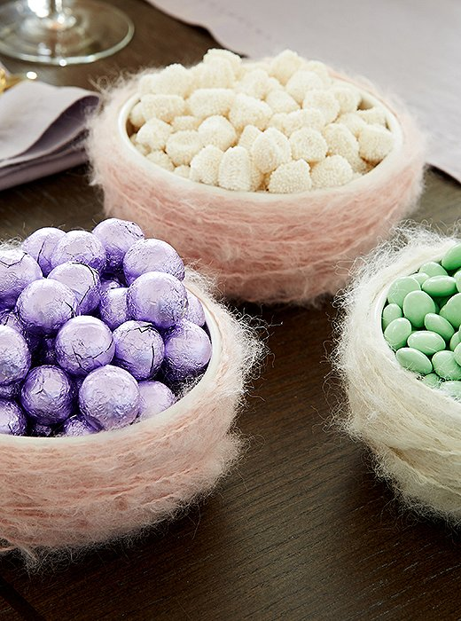"A few handmade touches will add charm and whimsy to your Easter fete—but they don't have to be complicated. Dylan loves these ""nests"" filled with foil-wrapped eggs and gummies, made by simply wrapping bowls with pastel yarn."