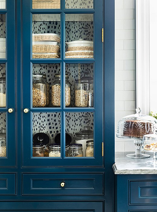 Les Touches appears again at the back of a kitchen cabinet reserved for dry goods and casual serveware—a simple trick that provides continuity between the two rooms.