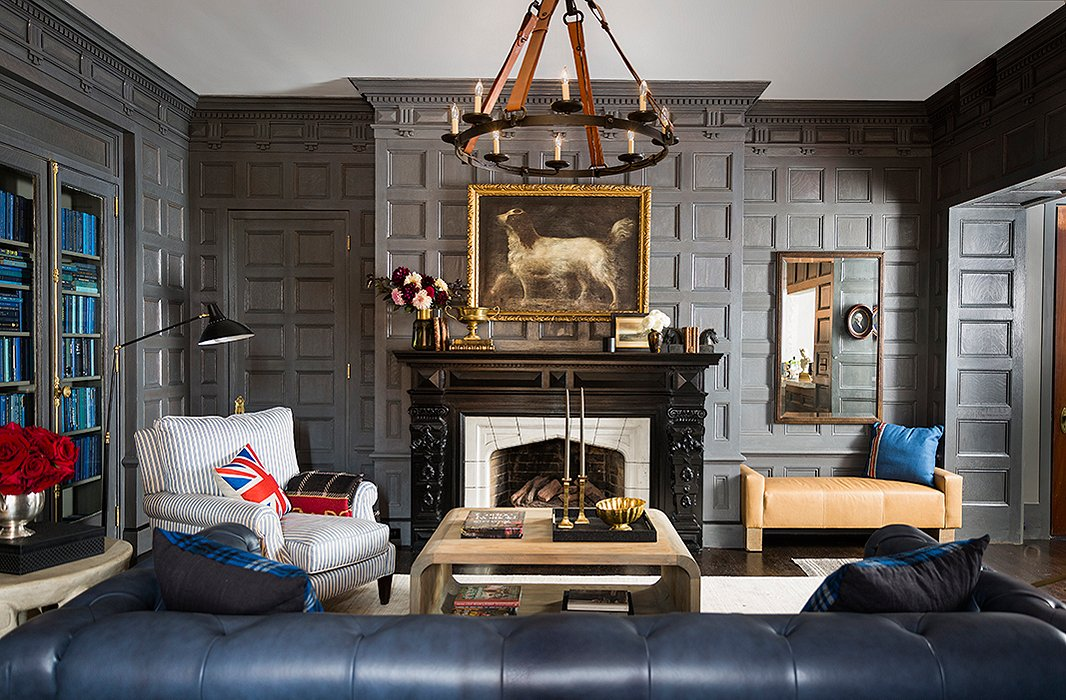 A prancing spaniel presides over the original Tudor-style mantel, given a fresh look with a brass trophy and stacks of vintage books. Beneath a rectangular mirror, a  leather bench by Brownstone Upholstery makes for a cozy fireside perch.