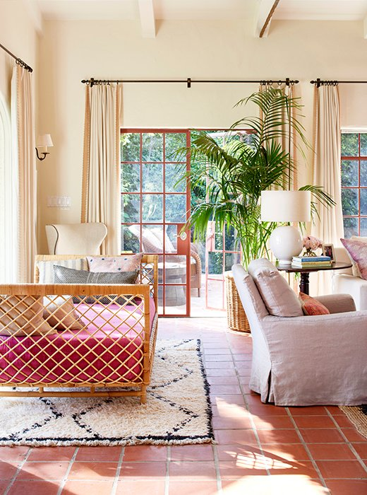 Nicole wrapped a daybed with raffia and anchored it with a Moroccan rug. The pink upholstery is a fashion-inspired hue, which works perfectly with the Saltillo tile floors.