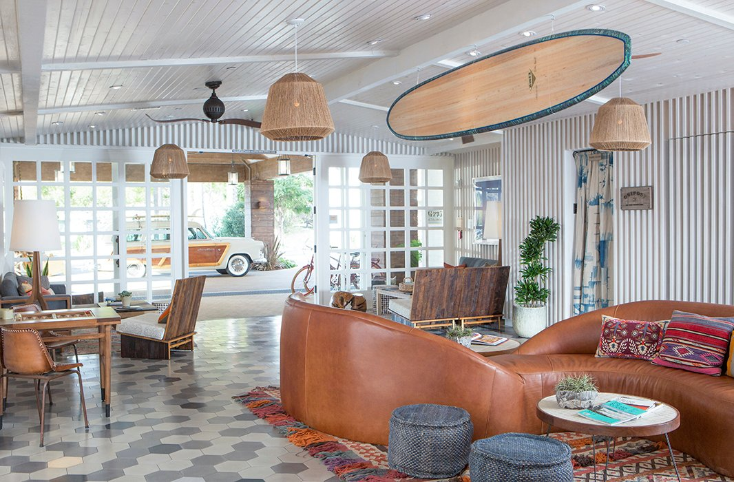 A surfboard hanging from the ceiling, a curved leather sofa… This is no ordinary hotel lobby. Photo courtesy of The Goodland.