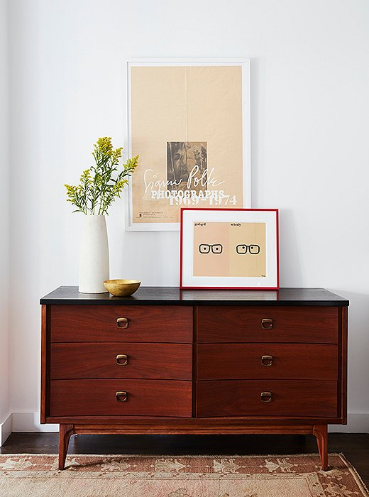 Yesteryear's nightstands meet their match with a black-top dresser. The Godard | Woody Allen print was Mindy's own. Note the red frame, which was chosen to contrast with the room's peachier hues, as seen in the print itself and the Oushak rug below.