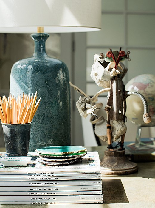 A table lamp by AERIN makes for alluring lighting on Rachel's desk alongside a wooden sculpture by Haitian artisans.