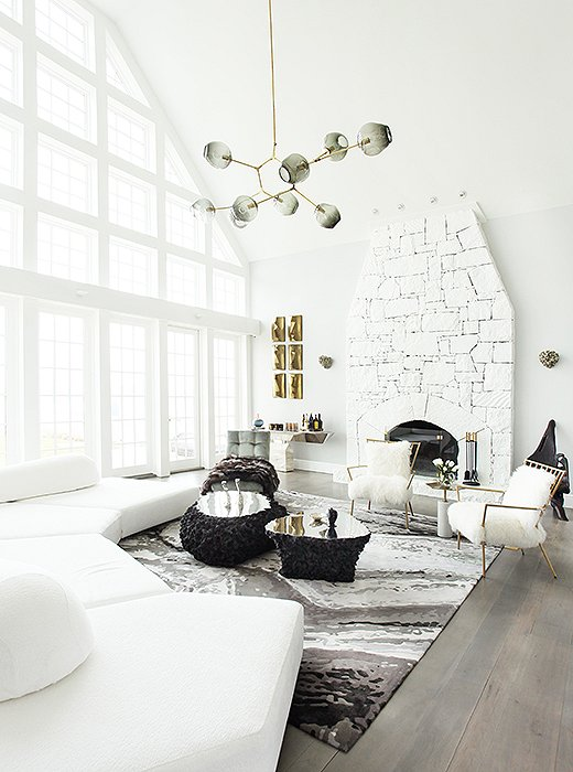 "In the living room, a double-height ceiling and a wall of windows called for pieces with a bit of drama. An oversize Edward Fields rug printed to resemble a pebbled riverbed anchors coffee tables made of molten lava and a structured sectional. ""Fur [real or faux] is an easy way to bring an element of nature into any room,"" says Sasha, which is why she chose two chairs upholstered in Mongolian sheepskin and a silver-fox throw to drape over the Milo Baughman chaise. Find a similar throw (this one faux) here."