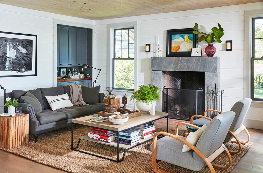 A gray linen sofa and pair of vintage Italian armchairs from Finch Hudson in Hudson, NY, create an inviting gathering spot by the fireplace. On the bluestone mantel, a small finger painting by T.R.'s niece rests alongside another titled The Bather. T.R. found the two-tier coffee table on One Kings Lane.