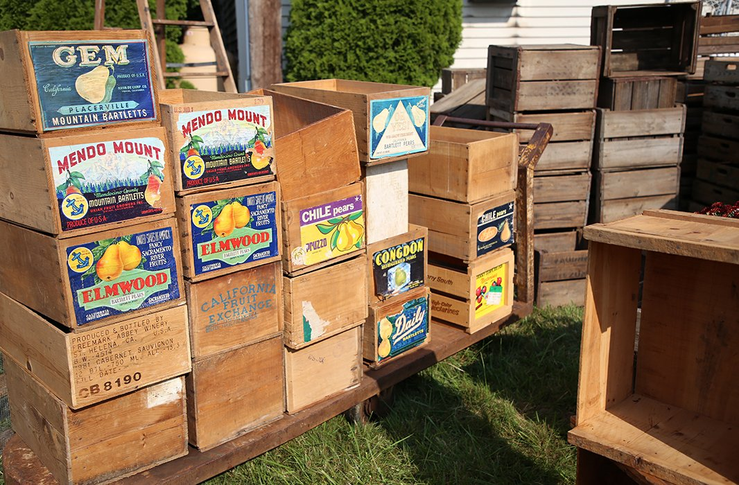 Vintage storage and packaging items, such as Coca-Cola crates, woven baskets, and boxes for transporting fruit, are a common sight at the show.