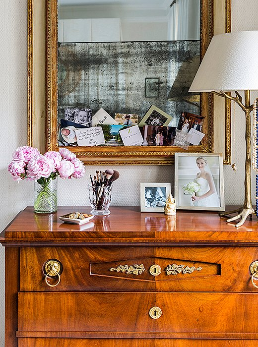 "A Biedermeier chest with a fold-down drawer serves as CeCe's bedroom vanity. She tucks personal mementos and photographs into the mirror above: ""Just little things that make me happy."""