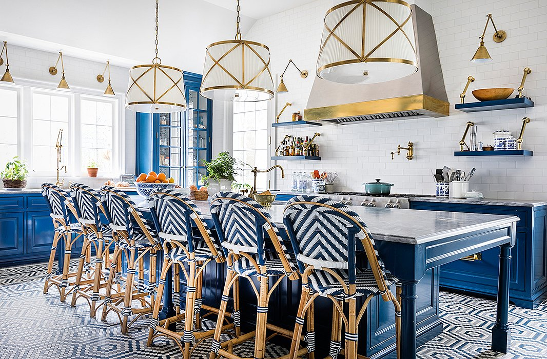 What was once a garage is now the kitchen. Hexagonal encaustic-tile floors draw from the hues of the cabinetry and the Gris de Savoie marble countertops. Brass pendants, sconces, and an exposed-steel range hood add reflective flair, while blue-and-white bistro stools encourage guests to pour a cup and stay awhile.