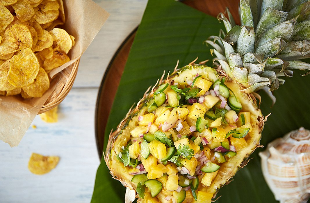Scooped, then served, the pineapple becomes both the meal and the serving dish, popping against a sheath of a banana leaf and a wood tray.