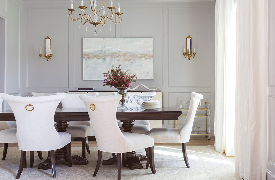Paneled wall moldings and brass fixtures give the formal dining room a sense of grandeur. Photo by Julie Soefer.