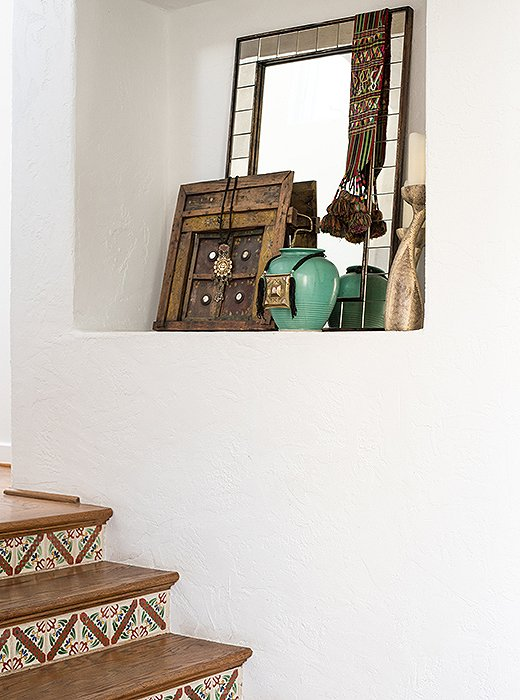 An artfully curated collection fills a nook above the tiled stairs.