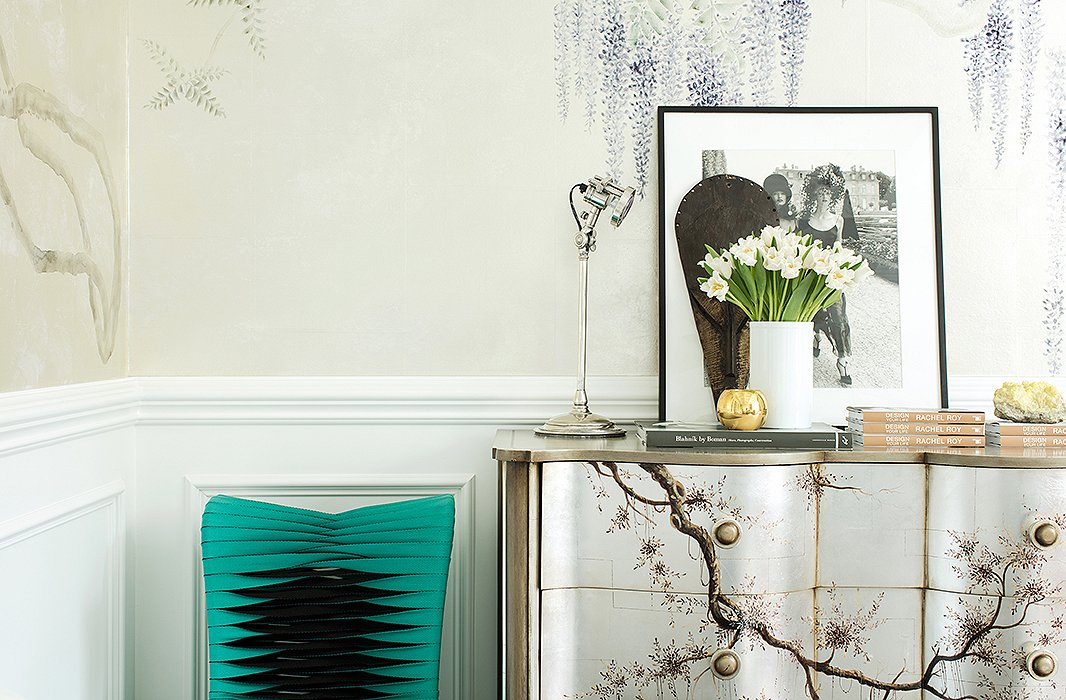 Reiterating her balance of edge and softness, a turquoise chair made from seat belts is placed next to a chest, hand-painted with romantic branching florals that nod to the wallpaper, that holds all of Rachel's office essentials.