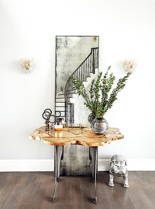 """The foyer hosts a petite console table backed by a floor-length mirror constructed of antiqued glass. """"The vignette has a bit of an Old World feel that works well in acountryside setting,"""" Sashanotes.Quartz sconces continue the glam theme while referencingthe geology of the surrounding area."""
